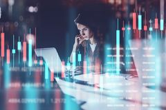 Business woman sitting at night office in front laptop computer with financial graphs and statistics on monitor. Red and royalty free stock photo