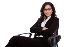 Business woman sitting in office chair. Attractive young caucasian business woman sitting in office chair with arms crossed. Isolated on white background Royalty Free Stock Images