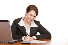 Business woman sitting in office signing contract. Attractive business woman sitting in office and signing contract. Isolated on white background Stock Photo