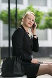 Business woman sitting outdoors with cellphone Stock Images