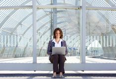 Business woman sitting outside and looking at laptop Royalty Free Stock Image