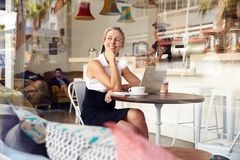 Business woman sitting in small coffee shop Stock Photography
