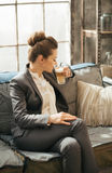 Business woman sitting on sofa and drinking coffee in loft Stock Photos