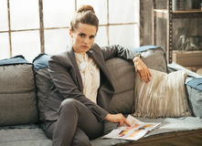 Business woman sitting on sofa in loft apartment Royalty Free Stock Images