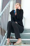 Business woman sitting on the stairs and talking on the phone Stock Images