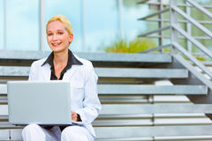 Business woman sitting on stairs and using laptop Royalty Free Stock Photography