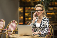 Business woman sitting in street coffee shops with a laptop and talking on a cell phone. Royalty Free Stock Image