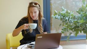 Business woman sitting at a table in a cafe drinking coffee and working on a laptop stock video footage