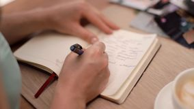 The girl takes a note in a close-up notepad. stock footage