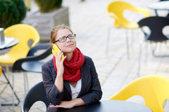Business woman sitting at a table in a cafe on the phone Stock Image