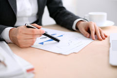 Business woman sitting at the table and examines the financial results Royalty Free Stock Photos