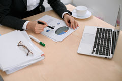 Business woman sitting at the table and examines the financial results Royalty Free Stock Photography