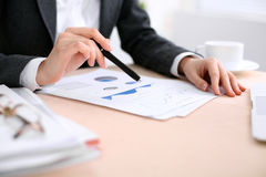 Business woman sitting at the table and examines the financial results Royalty Free Stock Images