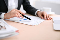 Business woman sitting at the table and examines the financial results Stock Photos