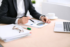 Business woman sitting at the table and examines the financial results Royalty Free Stock Image