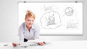Business woman sitting at table with hand drawn graph charts Royalty Free Stock Photography
