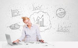 Business woman sitting at table with hand drawn graph charts Stock Image