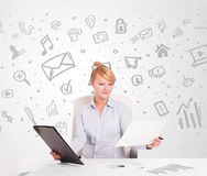 Business woman sitting at table with hand drawn media icons Royalty Free Stock Photography