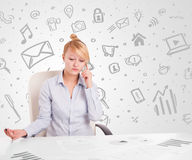 Business woman sitting at table with hand drawn media icons Royalty Free Stock Photos