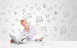 Business woman sitting at table with hand drawn media icons Stock Image