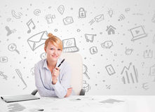 Business woman sitting at table with hand drawn media icons Stock Photography