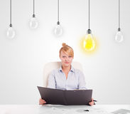 Business woman sitting at table with idea light bulbs Royalty Free Stock Photography