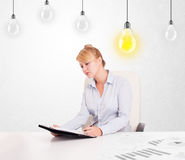 Business woman sitting at table with idea light bulbs Royalty Free Stock Photo