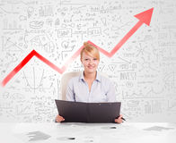 Business woman sitting at table with market diagrams Royalty Free Stock Photography