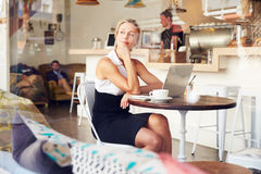 Business woman sitting at a table in small coffee shop Stock Photo