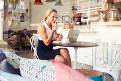 Business woman sitting at a table in small coffee shop Stock Photos