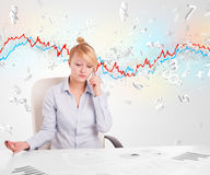 Business woman sitting at table with stock market graph Stock Images