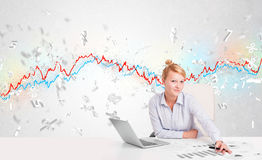 Business woman sitting at table with stock market graph Royalty Free Stock Images