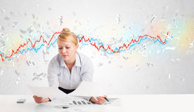 Business woman sitting at table with stock market graph Stock Photo