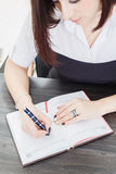 Business woman sitting at a table and writes the text in the notebook Stock Photo