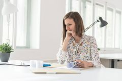 Business woman sitting thoughtfully staring at paperwork in an o. Ffice with a serious expression and her hand to her chin Stock Photo