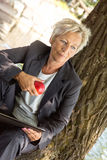 Business woman sitting on a tree and eating an apple Royalty Free Stock Images