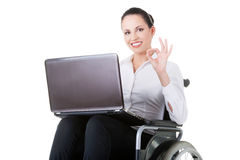 Business woman sitting on wheelchair, showing OK. Stock Photo