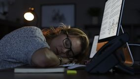 Business woman sleeping on computer at night. Mature business woman wearing eyeglasses leaning and sleeping on computer keyboard in office. Close up face of stock video footage