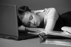Business woman sleeping in front of laptop. Young business woman sleeping in front of laptop Royalty Free Stock Photo