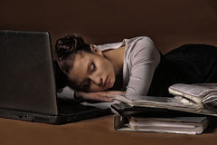 Business woman sleeping in front of laptop. Young business woman sleeping in front of laptop Royalty Free Stock Photos