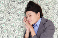 Business woman sleeping on money bed