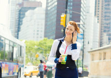 Business woman on smart phone in New York City, Manhattan. Walking on a street holding cup of juice smiling. Young professional female businesswoman in her 20s stock images