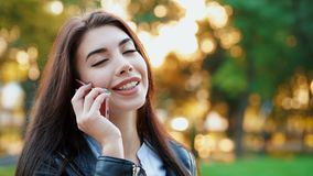 Business woman with smartphone close up in autumn park in sunset light. Girl have conversation with cell phone. Beautiful caucasian young woman talking with stock video footage