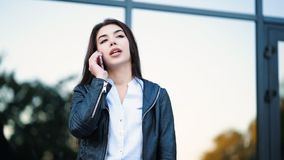 Business woman with smartphone close up near office building. Girl have conversation with cell phone. Beautiful. Caucasian young woman talking with mobile stock video