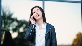 Business woman with smartphone close up near office building. Girl have conversation with cell phone. Beautiful. Caucasian young woman talking with mobile stock video footage