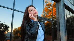 Business woman with smartphone close up near office building. Girl have conversation with cell phone. Beautiful. Caucasian young woman talking with mobile stock footage