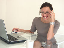 Business Woman with a smile. Smiling Business Woman on notebook PC, with cell phone and coffee Stock Photos