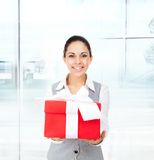 Business woman smile hold red gift box hands. Business woman happy smile hold red gift box in hands. Businesswoman in modern office Stock Image