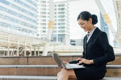 Business woman smile and sit on the staircase and typing word into laptop Royalty Free Stock Photography