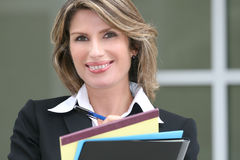 Business Woman Smiling. Business, corporate woman with folders, notepad and pencil, thinking about economic problems, outdoors royalty free stock image